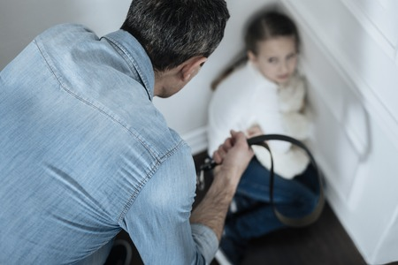 Aggression. Scared miserable fair-haired girl sitting in the corner while daddy holding a belt and beating her Stock Photo