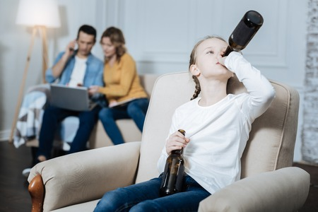 Drinking. Lonely blue-eyed little girl holding a bottle and drinking while her parents working on their laptops