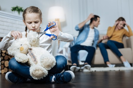 Brutal. Unhappy fair-haired little girl holding her teddy bear and cutting its paw while her parents shouting at each other Stock Photo