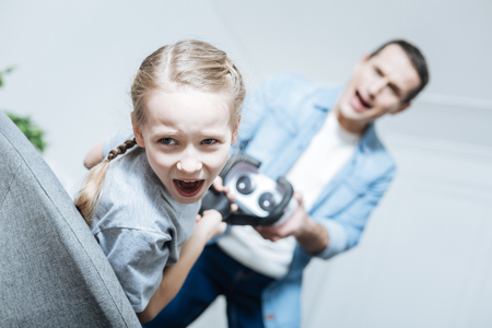 VR headset. Vexed blue-eyed little girl shouting and taking away her VR headset while daddy holding it