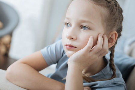 Thoughtful. Concentrated fair-haired blue-eyed little girl thinking and looking in the distance while sitting on the sofa