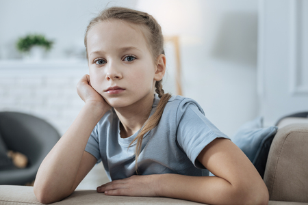 Sadness. Unhappy fair-haired blue-eyed little girl thinking and holding her head with her hand while sitting on the sofa Stock Photo