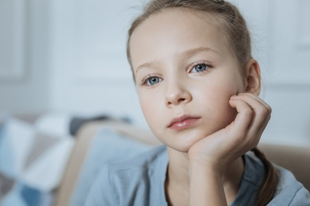 Thoughtful. Sad blond blue-eyed little girl thinking and holding her head with her hand while looking in the distance Stock Photo