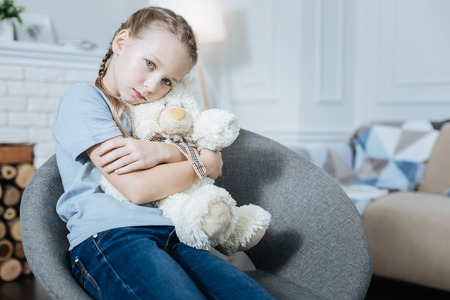 Favourite toy. Lonely fair-haired blue-eyed little girl hugging and holding her teddy bear while sitting in the armchair