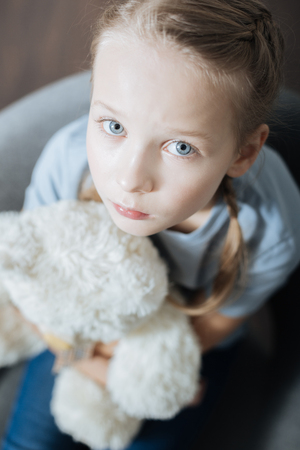 Feeling alone. Unhappy blue-eyed little girl hugging and holding her teddy bear while sitting in the armchair