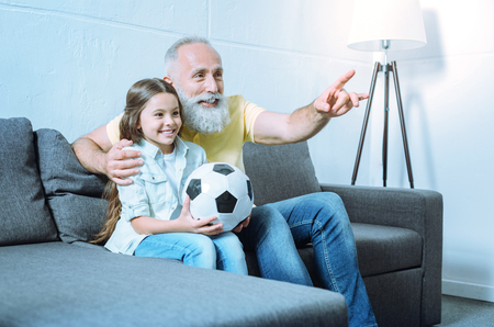 Transmitting knowledge. Careful senior gentleman embracing his adorable granddaughter and pointing toward a TV screen while both sitting on a sofa and talking about football.