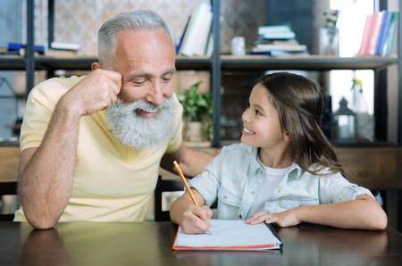 知ってたの?孫娘の話を聞きながら微笑む喜びに満ちた先輩紳士は、ノートのページに彼の注意を集中した。 写真素材