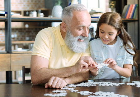 Let me see. Waist up shot of smart little girl standing next to her granddad and showing him two puzzle pieces while both playing at home. Banco de Imagens - 94039373