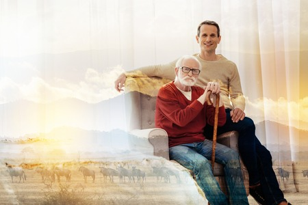 Close relatives. Calm serious aged man sitting in a comfortable armchair with his hands on a walking stick while his young handsome son sitting next to him and smiling Stock Photo