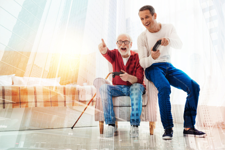 Having fun. Emotional excited senior man feeling happy while sitting in an armchair and playing games with a help of game console together with his smiling young son