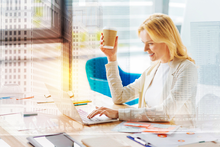 Successful worker. Portrait of optimistic woman expressing delight while drinking tea and working with a laptop Stock Photo
