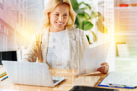 Future orientated. Close up of delighted woman sitting at the table while using a laptop and looking at smartly designed business plan Stock Photo