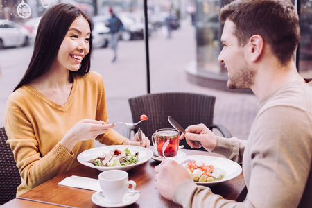 Second date. Positive optimistic smart couple enjoying dinner while flirting and smiling