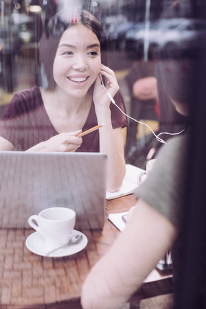 Great song. Charming cheerful female student pointing with pencil while smiling and holding headphone Stock Photo
