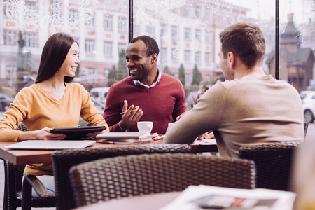 Business strategy. Jolly appealing three colleagues discussing strategy while laughing and sitting at cafe