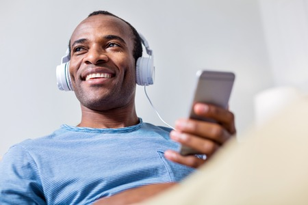 My playlist. Nice positive adult man wearing headphones and smiling while listening to his favourite song Stock Photo
