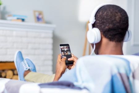 Favourite music. Nice positive cheerful man using his smartphone and listening to music in headphones while sitting on the sofa