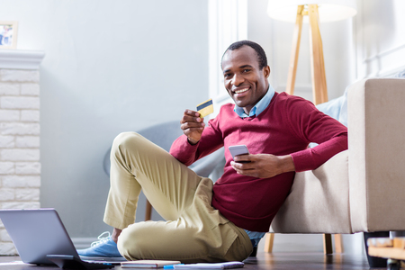 Mobile banking. Cheerful nice delighted man smiling and using a credit card while looking at you