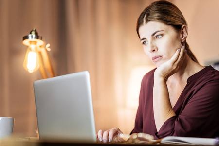 Let me think. Dreamy brunette touching her face while reading news and being at home Stock Photo