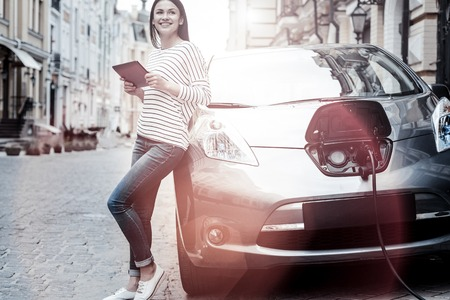 Conserving energy future. Positive minded young brunette smiling cheerfully while leaning on her car and browsing the Internet on her digital tablet during an electric automobile charging session.