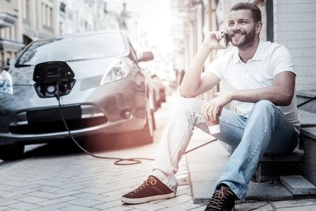 Hallo ich bin es. Positiver gesinnter tausendjähriger strahlender Kerl beim Trinken des Kaffees und Hören auf seinen Freund, der am Telefon mit seinem modernen Elektroauto auflädt im Hintergrund spricht.