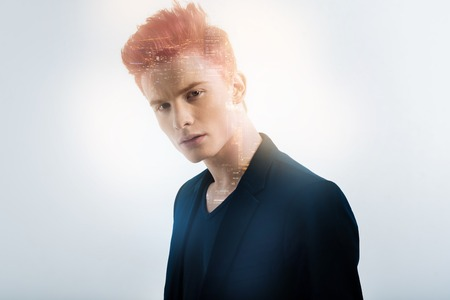 Im a leader. Perspective young redhead man spending time in the specious bright room looking straight and thinking.
