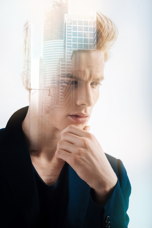 Difficult situation. Redhead thoughtful stylish man standing in the empty room touching his chin and thinking.