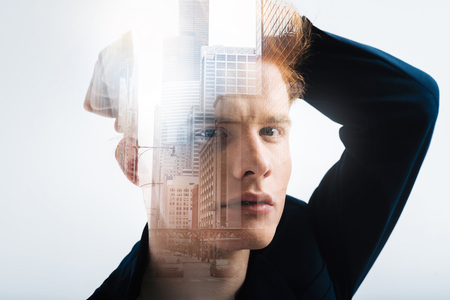 World in my eyes. Thoughtful redhead stylish man looking straight holding hand behind head and touching his hair.