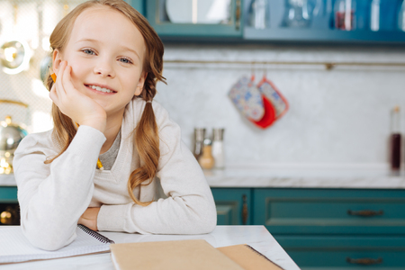 Attractive exuberant fair-haired girl smiling and sitting at the table with her notebook and holding a pencil Stock Photo