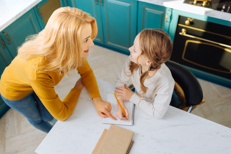 Good-looking glad blond slim mother smiling and looking at her daughter sitting at the table with her notebook Stock Photo