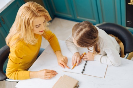 Pretty loving caring blond mother wearing a yellow sweater doing homework with her daughter while sitting at the table