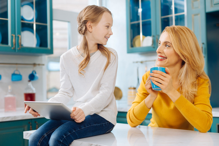 Beautiful exuberant fair-haired slim mother smiling and holding a cup of tea and her daughter using a tablet while sitting on the table