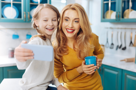 Attractive joyful fair-haired slim mother smiling and holding a cup of tea while her daughter taking selfies