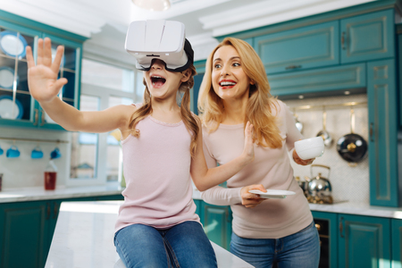 Beautiful exuberant fair-haired girl smiling and wearing VR headset while her mother standing behind her with a cup