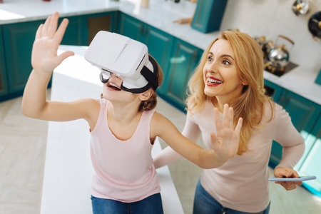 Beautiful glad fair-haired girl smiling and wearing VR headset while her mother standing behind her with a phone Stock Photo