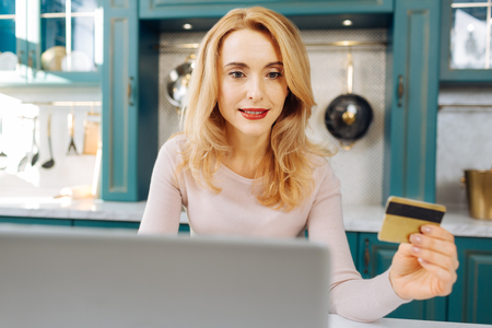Pretty inspired fair-haired young woman holding a card and working on her laptop while sitting in the kitchen Stock Photo