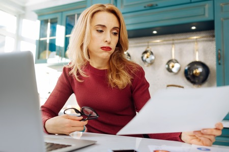 Pretty preoccupied blond young woman holding glasses and a looking at a sheet of paper while sitting at her laptop Stock Photo
