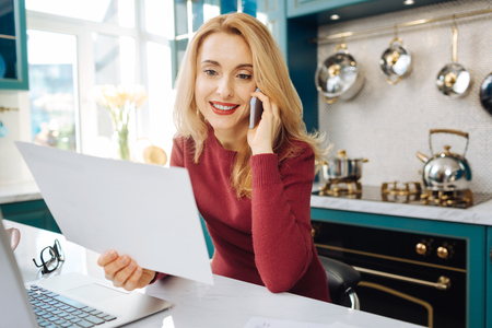 Attractive joyful blond young woman smiling and holding a sheet of paper and talking on the phone while sitting at her laptop