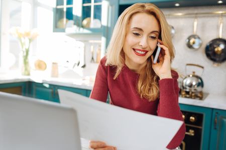 Pretty inspired blond young woman smiling and holding a sheet of paper and talking on the phone while sitting at her laptop Stock Photo