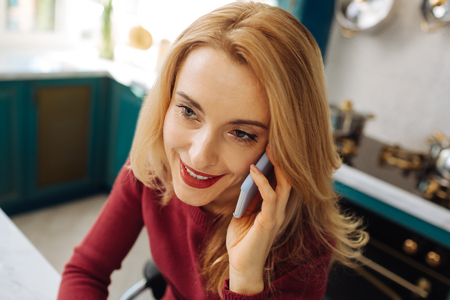 Pretty exuberant fair-haired young woman smiling and talking on the phone and wearing a red sweater