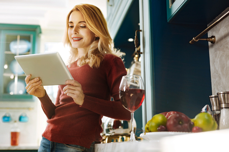 Pretty alert fair-haired young woman smiling and holding her tablet while a glass of wine standing on the table 版權商用圖片