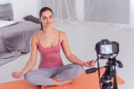 I love yoga. Attractive cheerful athletic dark-haired blogger smiling and doing yoga on the carpet while making a video for her blog