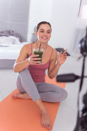 I love juice. Beautiful cheerful athletic dark-haired young woman smiling and drinking fresh juice while sitting and making a video for her blog