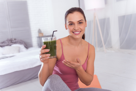 I adore juice. Good-looking exuberant athletic dark-haired young woman smiling and holding a glass of fresh juice while sitting Stok Fotoğraf