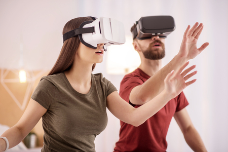 Virtual object. Pleasant glad charming couple stretching hands while putting on VR glasses and posing on the blurred background Stock Photo