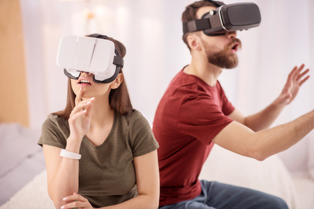 Unbelievable world. Thoughtful musing wistful woman touching face while putting on VR headset and looking up Stock Photo