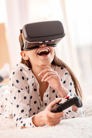 Sincere laugh. Appealing sincere kind woman holding controller while touching face and chortling