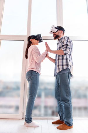 First try. Low angle of young positive nice couple taking each other hands while using VR glasses and standing near window