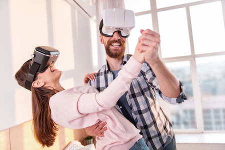Sweet dance. Cheerful jolly positive couple wearing VR glasses while dancing and smiling