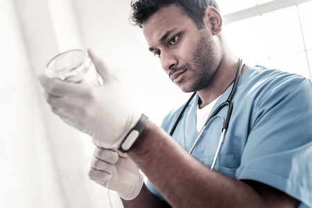 Finishing touches. Concentrated male medical worker preparing a drip for his patient and adjusting everything at hospital. Stock Photo